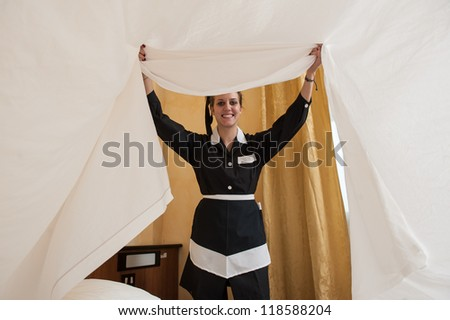 Chambermaid woman changing sheets in a hotel room. - stock photo