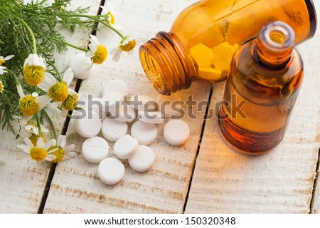 Chamomile and bottle with pills on white table. Concept of homeopathy. Selective focus.