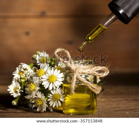 Chamomile essential oil and bouquet of chamomile flowers on wooden background - stock photo
