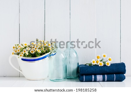 Chamomile flowers in vintage ceramic gravy boat, glass bottles and navy linen towels on white wooden background, home kitchen rustic decor - stock photo