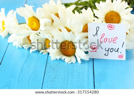 Chamomile flowers on a blue wooden background - stock photo