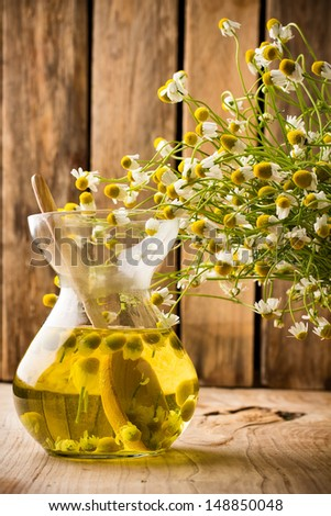 Chamomile flowers on a wooden surface. Chamomile aromatherapy, oil. - stock photo