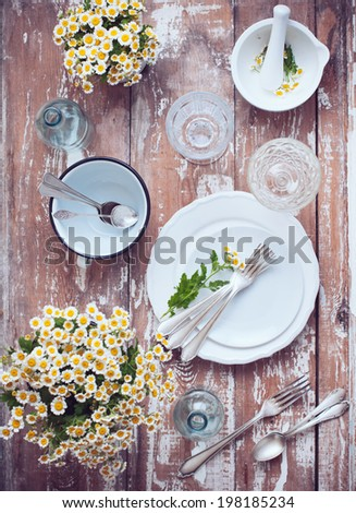 Chamomile flowers, white enamel cookware, glass bottles, vintage cutlery on a wooden background, home decor rustic table setting - stock photo