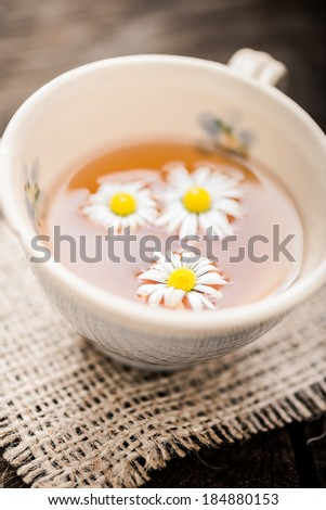 chamomile tea in a glass cup on wooden background