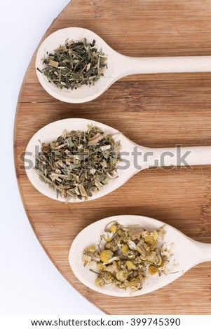 Chamomile tea nettle and basil on a wooden spoon.