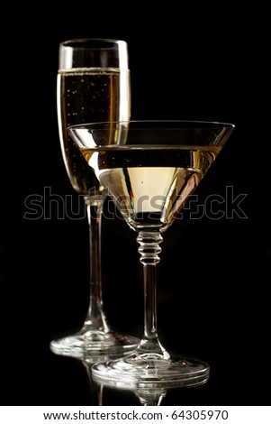 Champagne and martini glasses isolated on black - stock photo