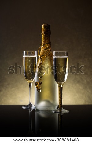 Champagne bottle and champagne glass in holiday setting - stock photo