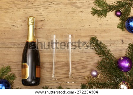 Champagne bottle, champagne glasses and fir twigs on wood - stock photo
