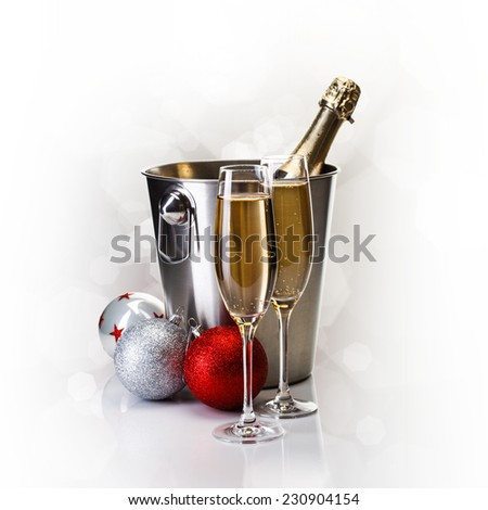 Champagne bottle in bucket with glasses of champagne and christmass balls in front of bokeh background - stock photo