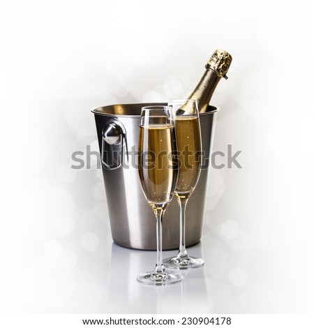 Champagne bottle in bucket with glasses of champagne in front of bokeh background - stock photo