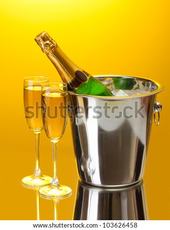 Champagne bottle in bucket with ice and glasses of champagne, on yellow background - stock photo