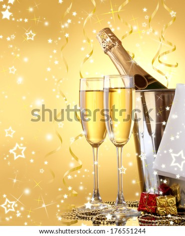 Champagne bottle in bucket with ice and glasses, on yellow background with lights