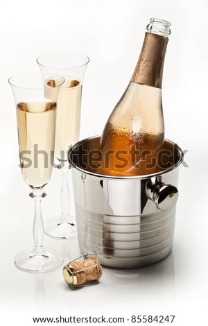 Champagne bottle in cooler and two champagne glasses. Isolated on a white. - stock photo