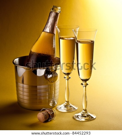 Champagne bottle in cooler and two champagne glasses. Isolated on a yellow. - stock photo