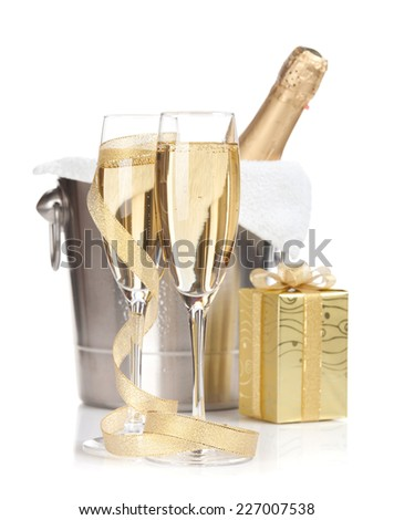 Champagne bottle in ice bucket, two glasses and christmas gift. Isolated on white background - stock photo