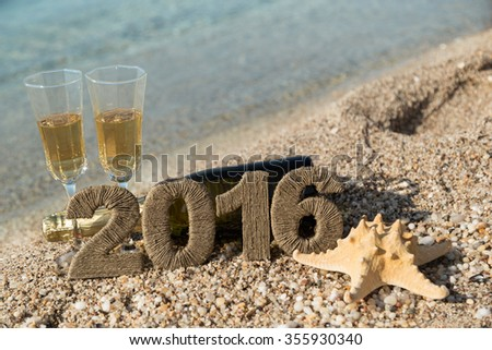 Champagne bottle lying on the beach with two champagne glasses, starfish and cardboard numbers 2016 placed next to it. Seascape in the background. - stock photo