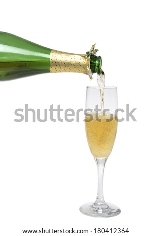 champagne bottle pouring into tall glass  - stock photo