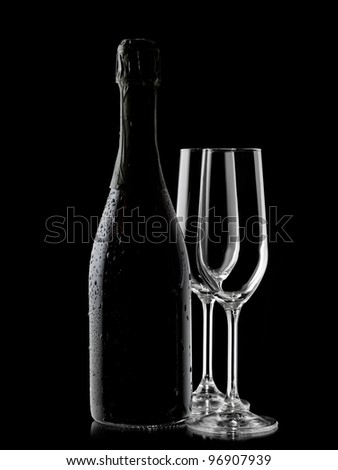 Champagne bottle with drops and two glasses - stock photo
