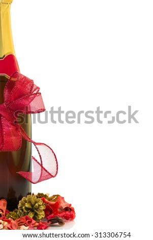 Champagne bottle with red Christmas bow and decoration over white background with copy space.