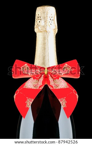 Champagne Bottle with Red Holiday Bow on Black Background