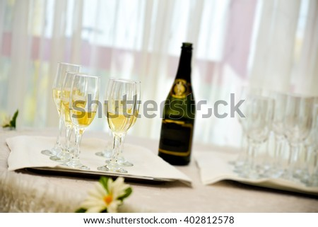 Champagne bottle with six filled glasses