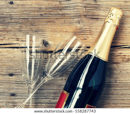 Champagne. Champagne bottle and two empty glasses on a wooden background. Valentine's Day. Birthday. Wedding. Anniversary. Rustic style.