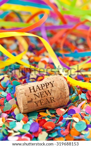 Champagne cork and party streamers on colorful confetti
