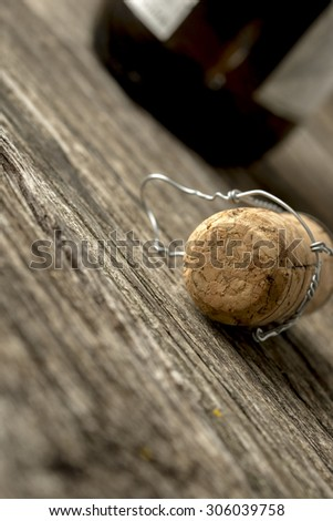 Champagne cork with attached wire lying on a rustic wooden table alongside a champagne bottle viewed at a very oblique tilted angle with copyspace. - stock photo