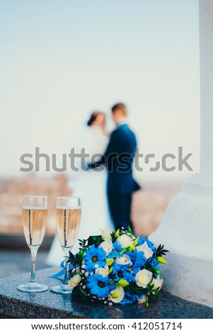 Champagne, flowers and kissing couple.