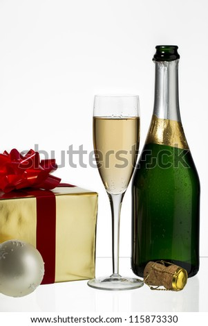 Champagne flute and bottle with Christmas gift and cork on white background