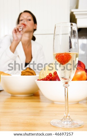 Champagne flute with a strawberry in it and a pretty brunette woman faintly in the background, representing a champagne breakfast on valentine's day - stock photo