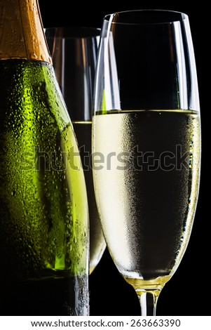 Champagne flutes and bottle on black background - stock photo