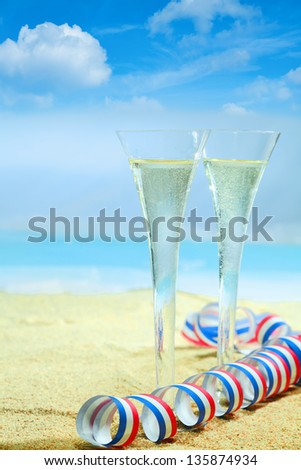 champagne flutes in elegant fluted glasses and a colourful red, white and blue twirled party streamer standing on the golden sand of a tropical beach with an azure blue ocean on a summer vacation. - stock photo