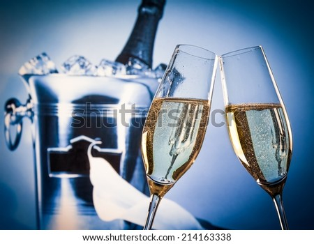 champagne flutes with golden bubbles make cheers in front of champagne bottle in bucket background - stock photo