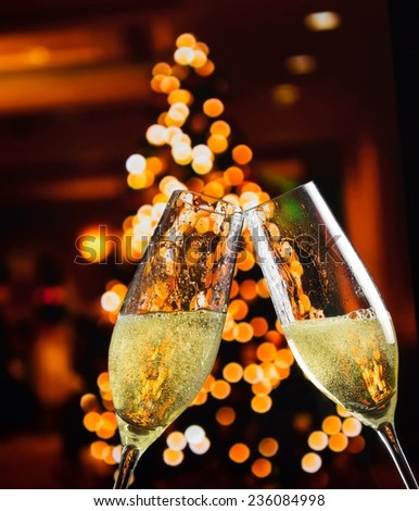 champagne flutes with golden bubbles make cheers on christmas lights decoration background, christmas atmosphere - stock photo