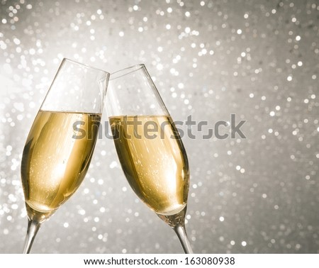 champagne flutes with golden bubbles make cheers on silver light bokeh background with space for text