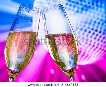 champagne flutes with golden bubbles make cheers on sparkling blue and violet disco ball background with space for text - stock photo