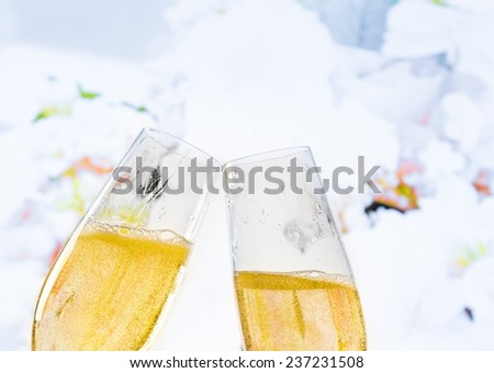 champagne flutes with golden bubbles make cheers on wedding flowers background - stock photo