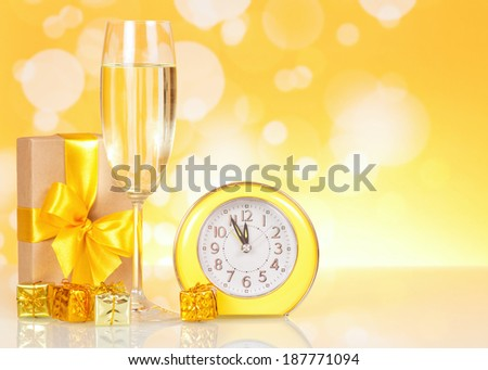 Champagne, gift clock showing time about midnight in yellow