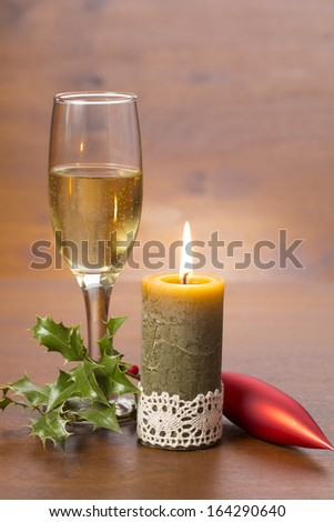 champagne glass and candle with christmas decoration on wooden