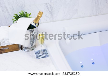 Champagne glass and Jacuzzi Spa with colourful light whirlpool - stock photo