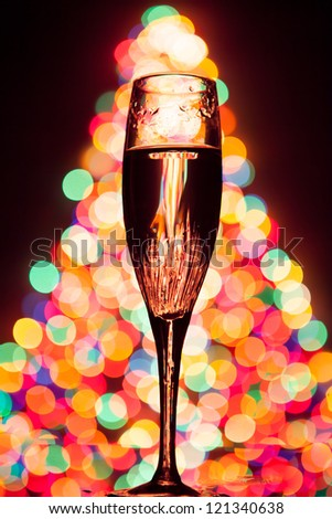 champagne glass silhouette against christmas tree bokeh - stock photo