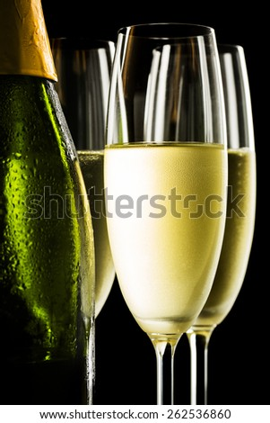 Champagne glasses and bottle on black background - stock photo