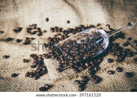 champagne glasses and coffee beans on traditional sack textile. - stock photo