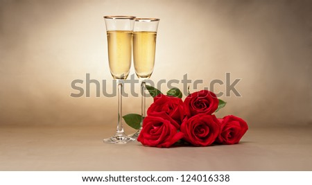 Champagne glasses and roses in front of beige background - stock photo