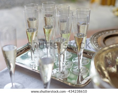 champagne glasses flutes on silver tray - stock photo