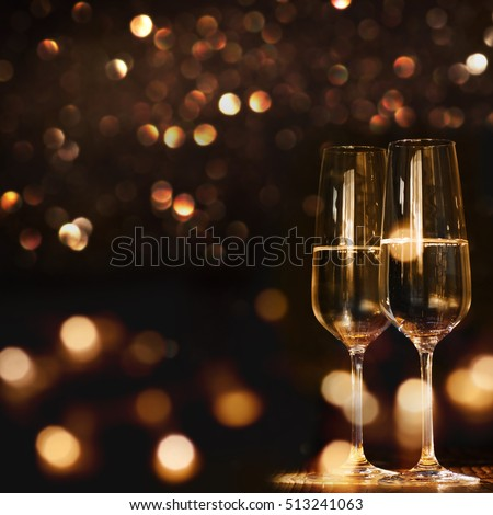 Champagne glasses for a new year against a dark background with gold shimmering light