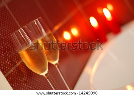 Champagne glasses on the edge of a candle-lit bath - stock photo