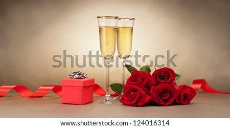 Champagne glasses, present and roses in front of beige background - stock photo