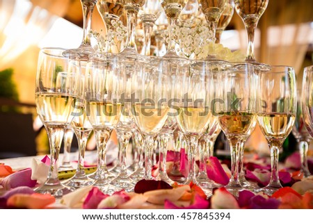 Champagne glasses. Wedding slide champagne for bride and groom outdoors. Colorful wedding glasses with champagne. Catering service. Catering bar for celebration. Beauty of bridal interior for wedding  - stock photo